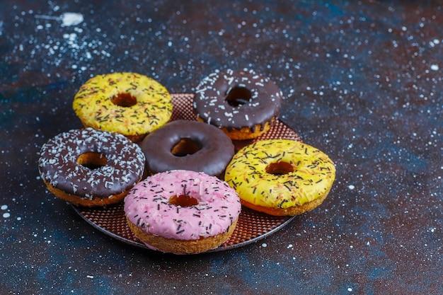 Ассорти из пончиков с шоколадной глазурью, розовой глазурью и посыпкой.