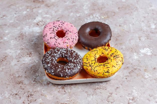 チョコレートのつや消し、ピンクの艶をかけ、振りかけるドーナツの盛り合わせ。