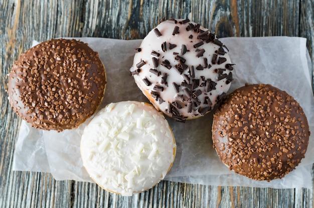Ассорти пончиков с шоколадной глазурью на деревянной поверхности