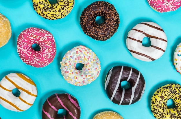 Assorted donuts with different fillings and icing on a blue back