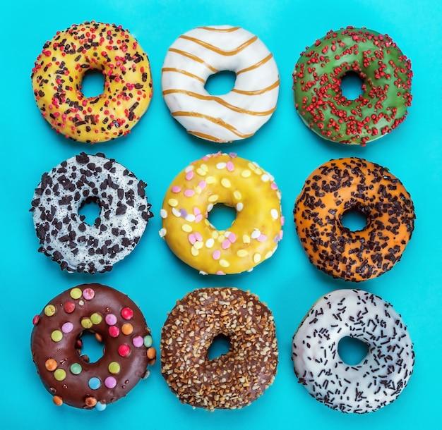 青い背景にアイシングが付いた各種ドーナツ。味の違うドーナツ盛り合わせの背景