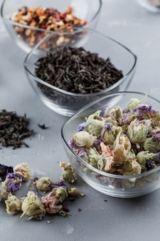 Assorted dried herbs in glass bowls close-up on a plaster surface