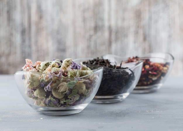 Assorted dried herbs in glass bowls high angle view on plaster and grungy surface