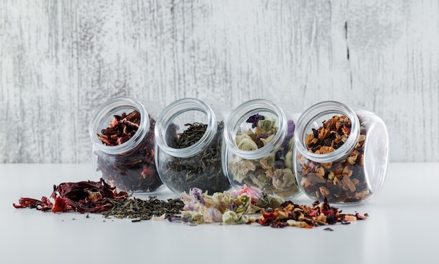 Assorted dried herbs in plastic jars on white and grunge surface