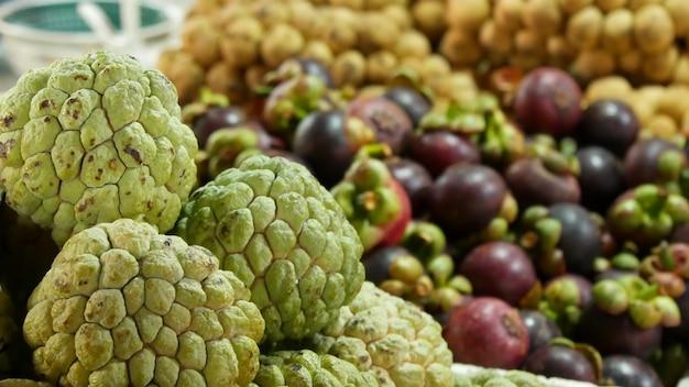 Ассорти из экзотических фруктов. сахарные яблоки, лонган и мангустин на рынке в тропической стране.