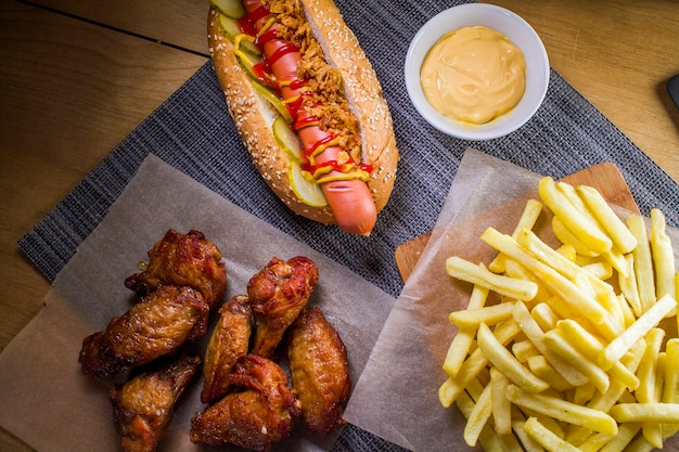 Assorted fast food hot dog, french fries, grilled wings and cheese sauce.