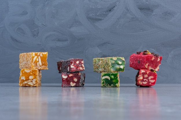 Assorted flavors of turkish delights displayed on marble background.