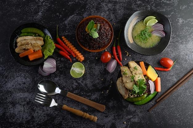 黒い石のテーブルに野菜、肉、魚の盛り合わせと料理。上面図。