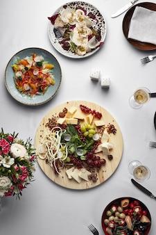 모듬 음식, 스낵이있는 연회 테이블, 흰색 테이블 위의 이탈리아 전채, 평면도, 모듬 소시지, 모듬 치즈, 와인, 절인 야채.