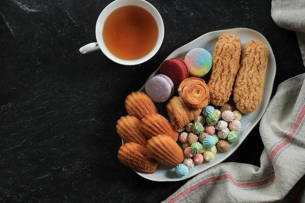 Ассорти из французской выпечки на белом мраморном столе для текста или рецепта. миндальное печенье, безе, мадлен, кракленовый эклер, мини-круассан, большое шоколадное печенье, место для текста