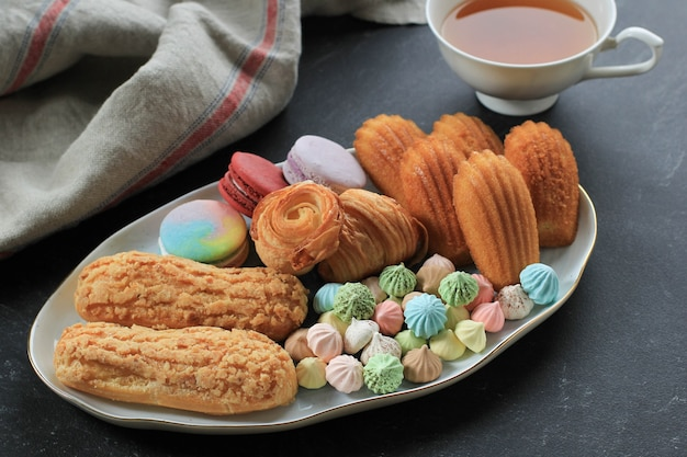 Ассорти из французской выпечки с копией пространства на белом мраморном столе для текста или рецепта. миндальное печенье, безе, мадлен, кракленовый эклер, мини-круассан, большое шоколадное печенье и чашка чая