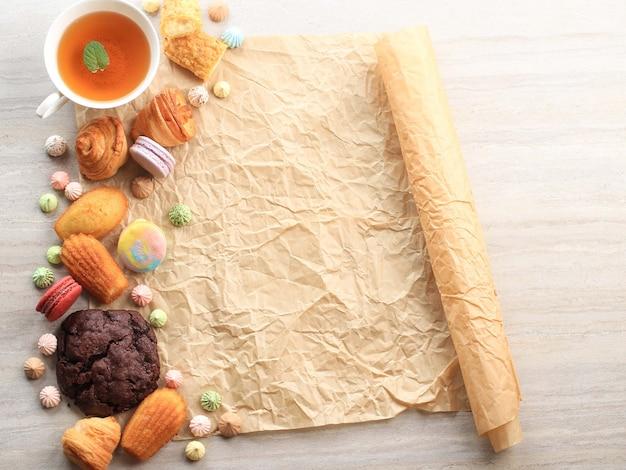 텍스트 또는 조리법에 대한 흰색 대리석 테이블에 복사 공간이 있는 모듬된 프랑스 과자. 마카롱, 머랭, 마들렌, craquelin eclair, 미니 크루아상, 빅 초콜릿 쿠키 및 차 한잔