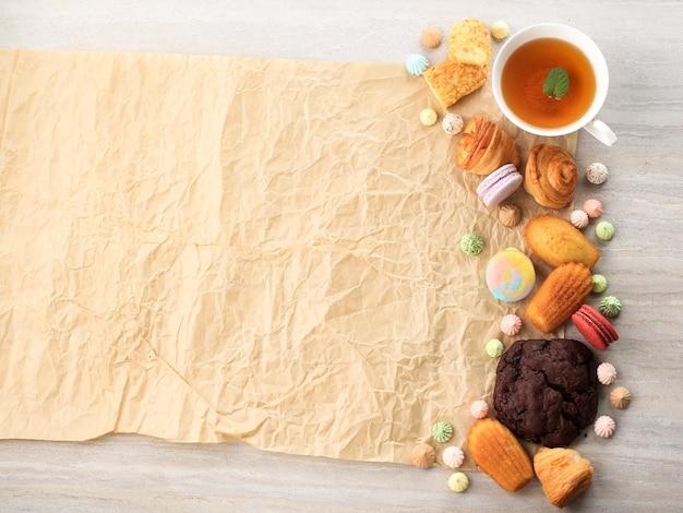 テキストまたはレシピ用の白い大理石のテーブルにコピースペースが付いた各種フレンチペストリー。マカロン、メレンゲ、マドレーヌ、クラケリンエクレア、ミニクロワッサン、ビッグチョコレートクッキー、お茶