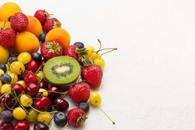 フレッシュベリーとフルーツの盛り合わせ。白い背景の上のアプリコットキウイストロベリーチェリーブルーベリー。減量のコンセプトトップビュー。コピースペース。