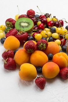 Assorted fresh berries and fruits. apricots kiwi strawberry cherry blueberry on white