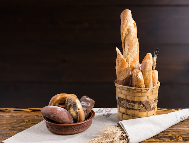 素朴なバスケットと後ろにコピースペースがある陶器のボウルのパン屋に展示されている焼きたてのパンとロールパンの詰め合わせ