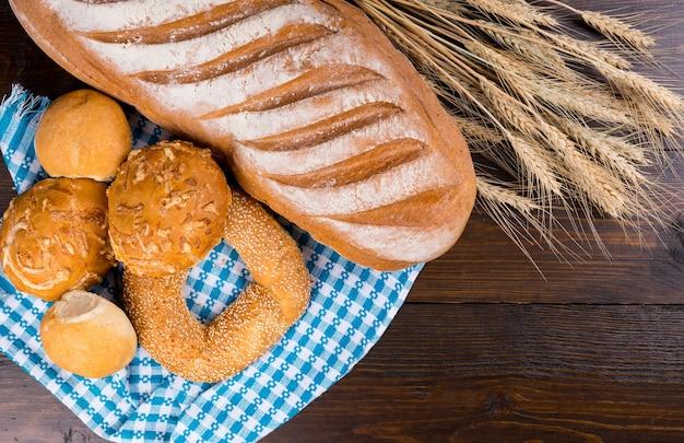 木製のテーブル、俯瞰図のカラフルな青と白の布に表示された小麦の耳と各種焼きたてのロールパンとバゲット