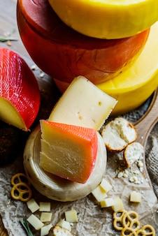 Ассорти свежих сыров и сырное колесо на разделочной доске. на деревянном фоне. выборочный фокус.