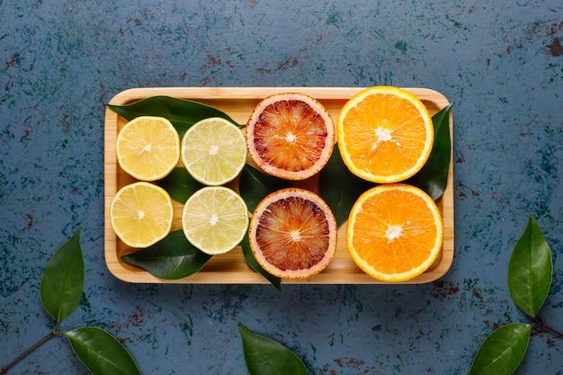 Ассорти из свежих цитрусовых, лимон, апельсин, лайм, кроваво-оранжевый, свежий и красочный, вид сверху
