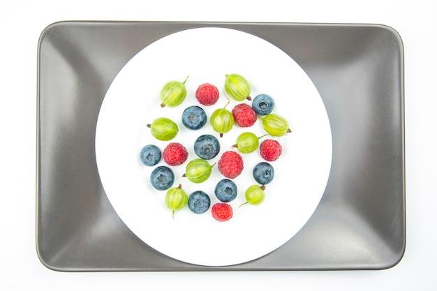 하얀 접시에 모듬 된 신선한 다른 열매입니다. 유용한 비타민 건강 식품 과일. 건강한 야채 아침 식사