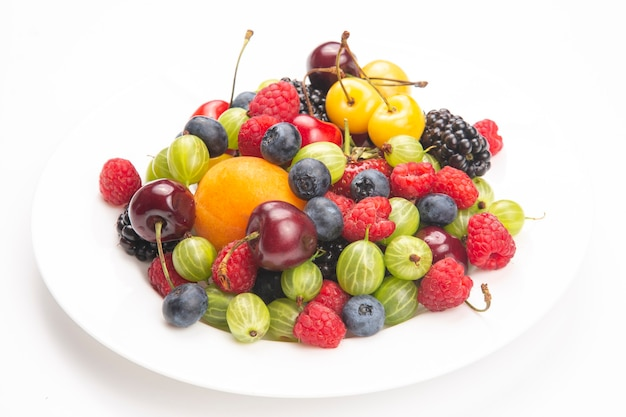 Assorted fresh different berries on a white plate. useful vitamin healthy food fruit. healthy vegetable breakfast