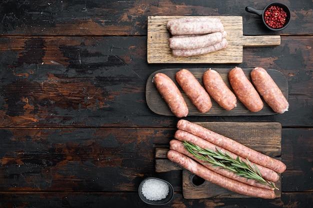 新鮮な生の豚肉、牛肉、鶏肉のソーセージの盛り合わせ、上面図、古い暗い木製のテーブル