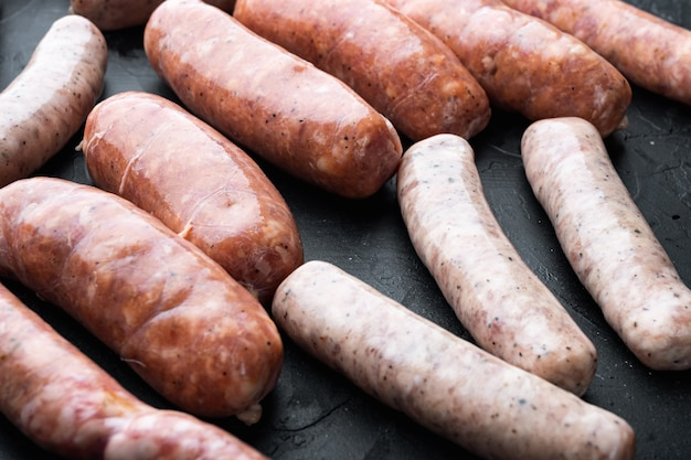 Assorted fresh raw pork, beef and chicken sausages, on black table