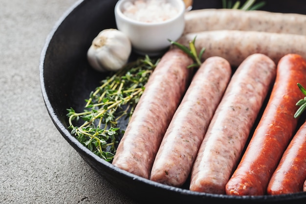 Assorted fresh raw sausages with thyme, rosemary and garlic in a cast iron pan on a dark concrete table.