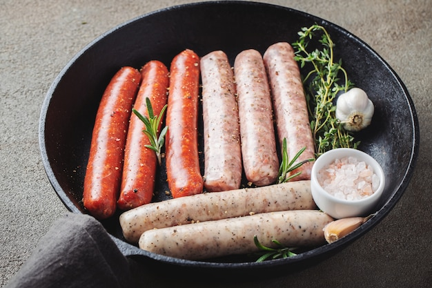 Assorted fresh raw sausages with thyme, rosemary and garlic.