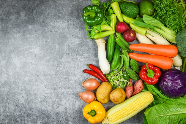 Assorted fresh ripe fruit red yellow purple and green vegetables mixed selection on gray background