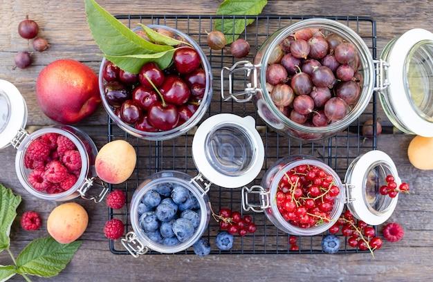 Ассорти из свежих сезонных ягод в стеклянных банках на старинном деревянном столе