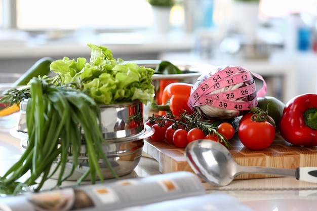 Assorted fresh vegetables kitchen photography. lettuce, rosemary and green onion in saucepan. tomato and cabbage wrapped in centimeter on wooden board. organic ingredient horizontal photography