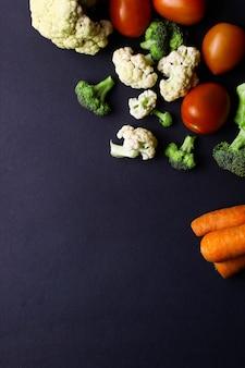 Ассорти из свежих овощей, помидоров, брокколи и моркови, изолированные на черном фоне