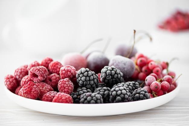 Ассорти замороженных ягод на белой тарелке