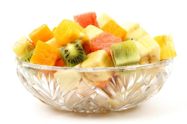 白い背景の上のプレートに立方体に刻んだフルーツの盛り合わせ。果物の便利なビタミン食品