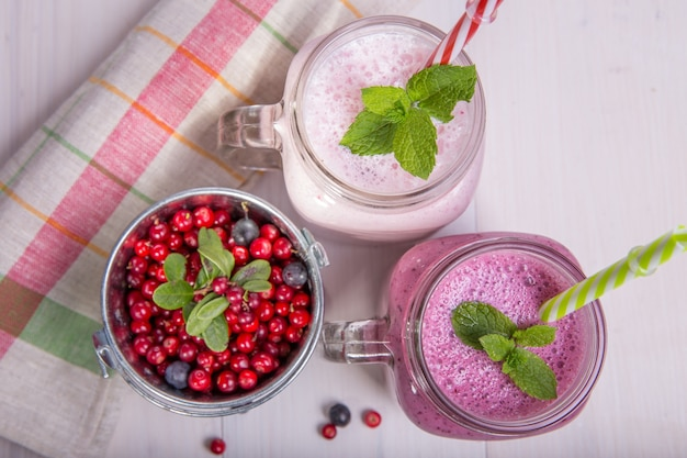 白いテーブルの上でフルーツやベリーの盛り合わせが揺れます。スムージーの健康的な食事の概念