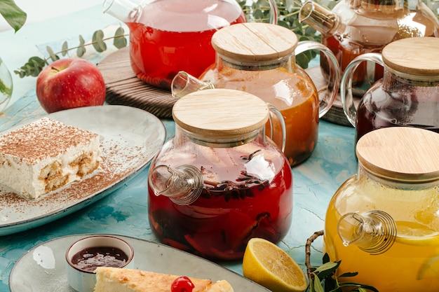 Ассорти фруктовый чай в стеклянных горшках на синем фоне