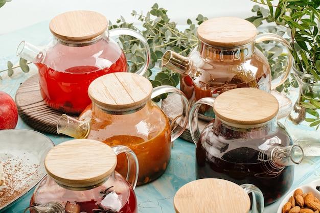 Ассорти фруктовый чай в стеклянных горшках на столе