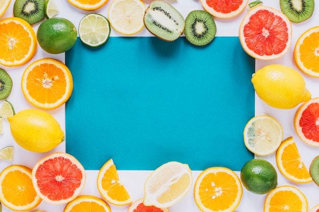 Assorted fruits around blue paper sheet