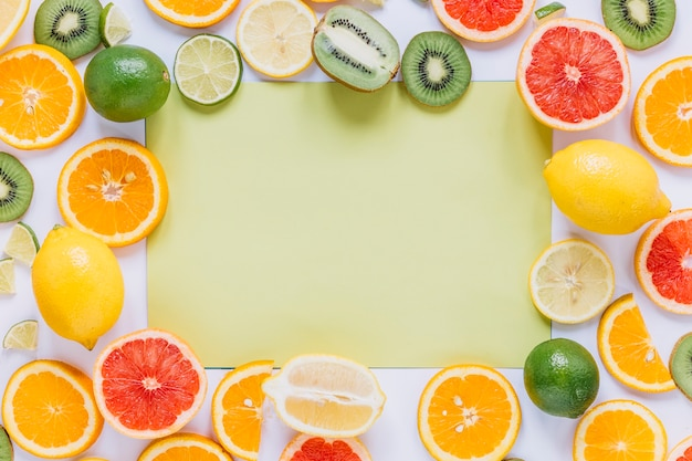 Assorted fruits around green paper sheet