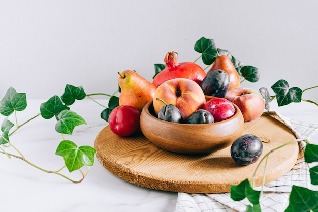 Assorted fruits in a wooden plate, green ivy mango, peach, plum, pear, pomegranate, fig peach