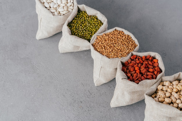 Assorted gluten free grains in linen cloth bags on grey background.