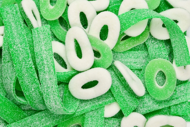Assorted green gummy candies background.