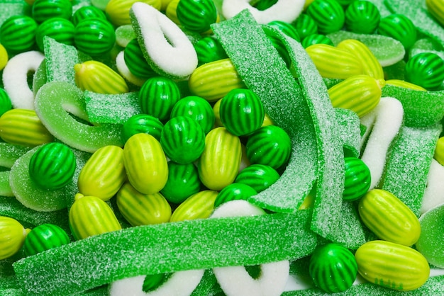Assorted green gummy candies surface