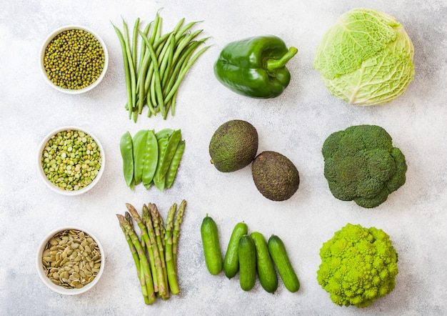 Assorted green toned raw organic vegetables. avocado, cabbage, broccoli, cauliflower and cucumber with trimmed and mung beans, pak choi, loose pepper and lettuce