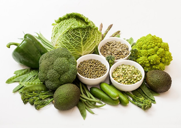Assorted green toned raw organic vegetables on white surface