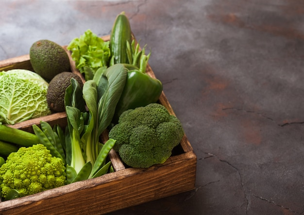 Assorted green toned raw organic vegetables in wooden box on dark stone table.