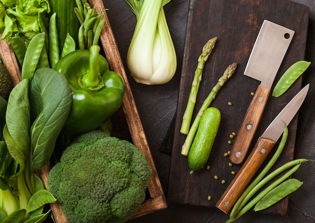 Assorted green toned raw organic vegetables in wooden box