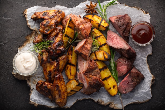 Assorted grilled meat and potatoes on black background