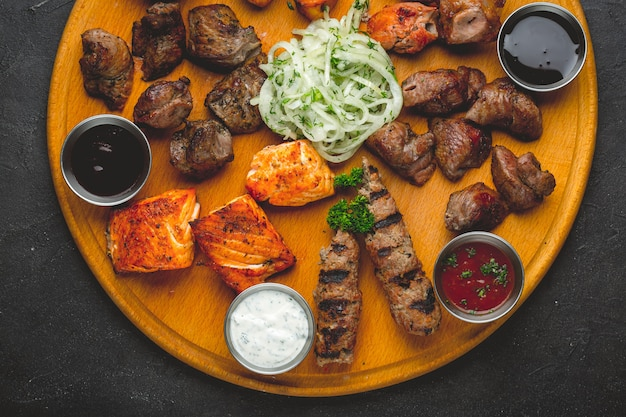 Assorted grilled meats and sauces on a wooden table.